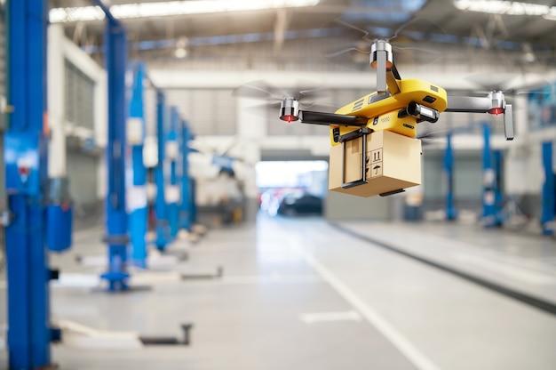 Vliegende bezorgdrone die pakketdoos overbrengt van distributiemagazijn naar de achtergrond van het klantenservicecentrum van de autogarage. modern innovatief technologie- en gadgetconcept.