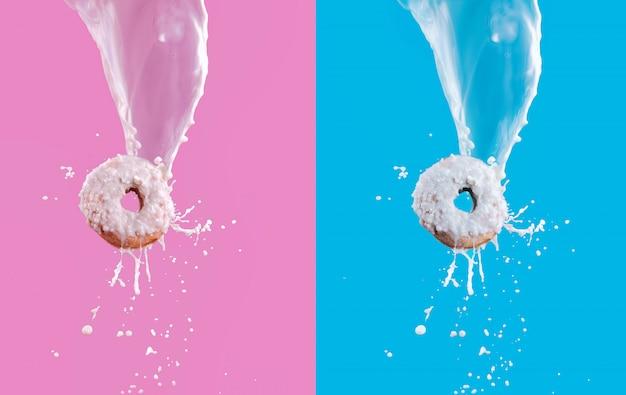 Vliegende donuts met witte verglaasde chocolade en melk het bespatten op roze en blauwe achtergrond. zoet eten concept