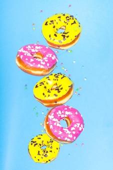 Vliegende donuts. roze en gele donuts met hagelslag op blauwe achtergrond
