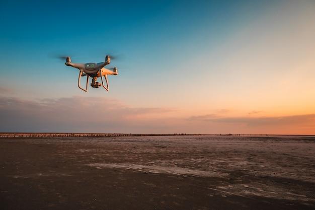 Vliegende drone op een achtergrond van zee zonsondergang