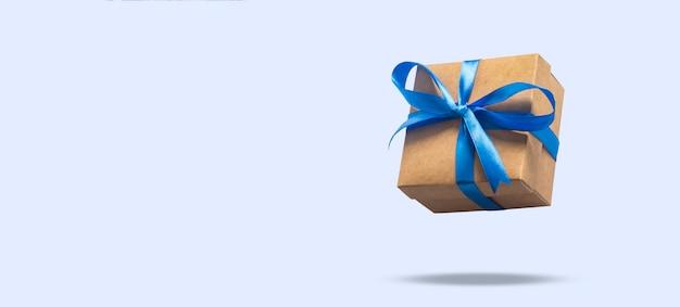 Vliegende geschenkdoos op een lichtblauwe ondergrond. concept vakantie, cadeau, verkoop, bruiloft en verjaardag.
