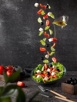 Vliegende groenten zijn de ingrediënten van een griekse salade op een donkere achtergrond met rekwisieten tegen de b