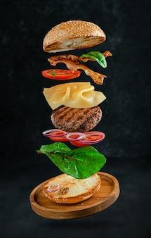 Vliegende hamburger met ingrediënten op donkere stenen ondergrond