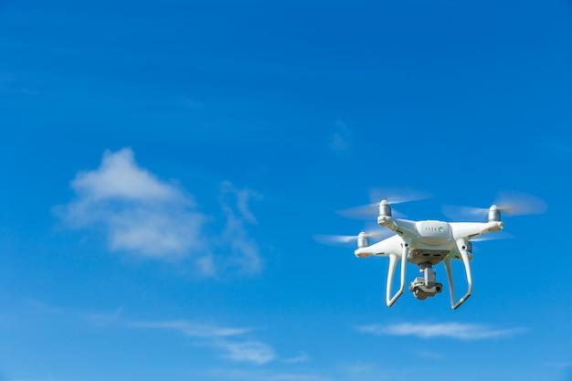 Vliegende hommel quadcopter met digitale camera op blauwe hemel