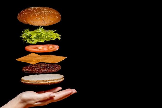 Vliegende ingrediënten hamburger of cheeseburger op een kleine houten snijplank geïsoleerd op een donkere achtergrond. burger zweeft in de lucht boven de tafel. ruimte voor tekst.