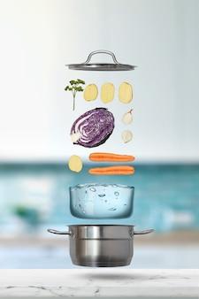 Vliegende ingrediënten voor het koken van groenten, bouillon of soep met potten, water op een wazige keukenachtergrond. gezond concept van vegetarisch eten.