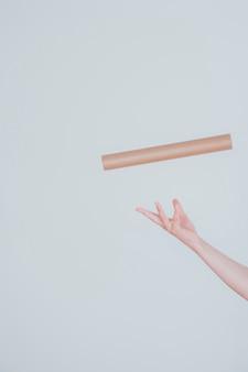 Vliegende kartonnen buis en hand