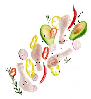 Vliegende kippenbenen met groenten en kruiden die op wit worden geïsoleerd