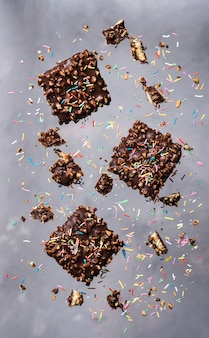 Vliegende koekjes. chocoladeschilfers met noten en suiker strooi stippen die in beweging vallen.