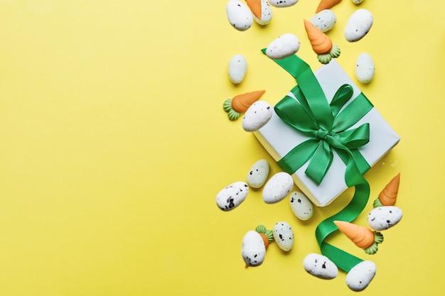 Vliegende kwarteleitjes en zoete wortel met geschenkdoos met groen lint op gele trendkleurentabel. spring happy easter vakantie bovenaanzicht.