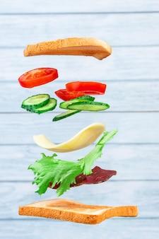 Vliegende lagen sandwich met ham, kaas en groenten