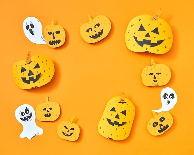 Vliegende papieren spoken en handgemaakte pompoenen in de vorm van een vierkant frame op een oranje achtergrond met ruimte voor tekst. lay-out voor briefkaart naar halloween