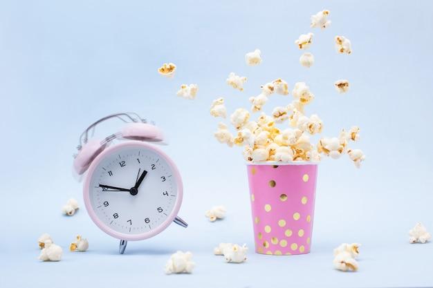 Vliegende popcorn in een helder glas en een bellende wekker op blauw