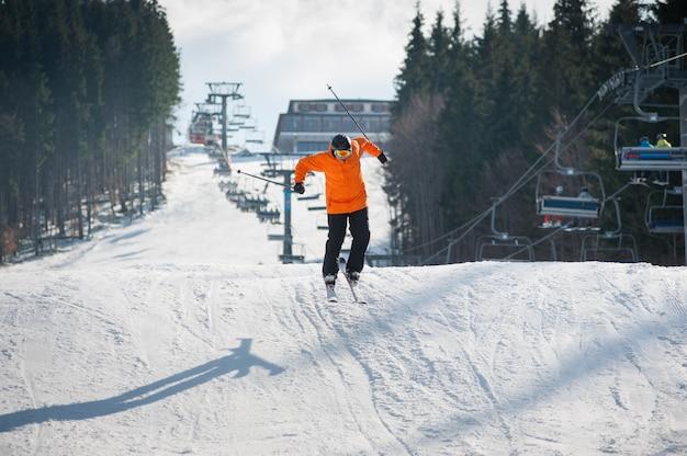 Vliegende skiër bij sprong van de helling van bergen in oranje jasje die een hoogspringen uitvoeren