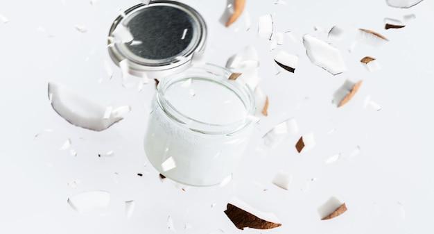 Vliegende stukjes kokosnoot rond kokosboter in glazen pot.
