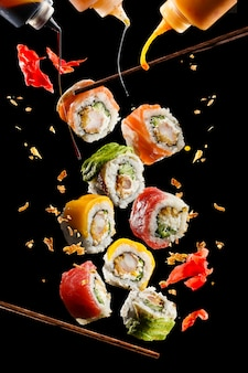 Vliegende stukjes sushi met houten stokjes en saus