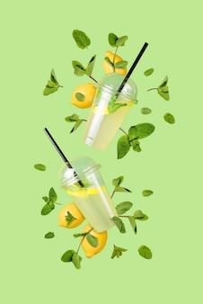 Vliegende verfrissende limonade uit een plastic beker met vliegende citroenen en muntblaadjes op een groene achtergrond