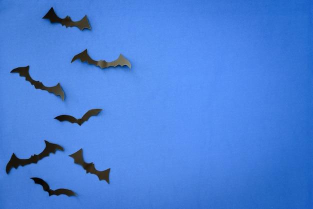 Vliegende vleermuizen op blauw