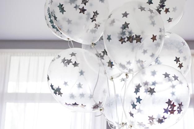 Vliegende witte ballonnen met zilveren sterren onder het plafond