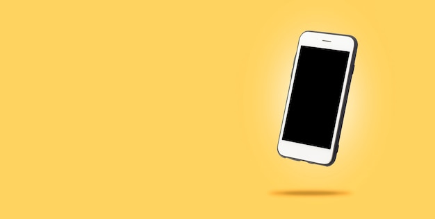 Vliegende witte mobiele telefoon op een gele ondergrond. levitatie. conceptapplicatie voor telefoon, mobiel apparaat, presentatie. .