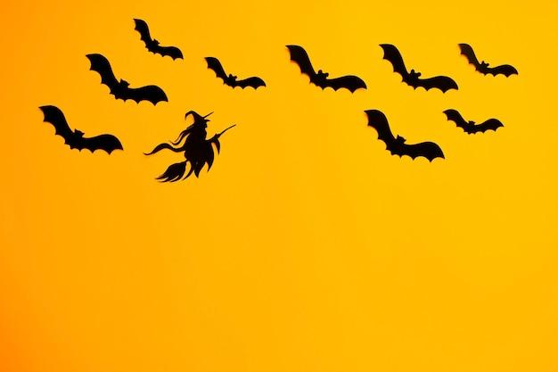 Vliegende zwarte vleermuizen en heks op een bezem. halloween-document decoraties op oranje achtergrond
