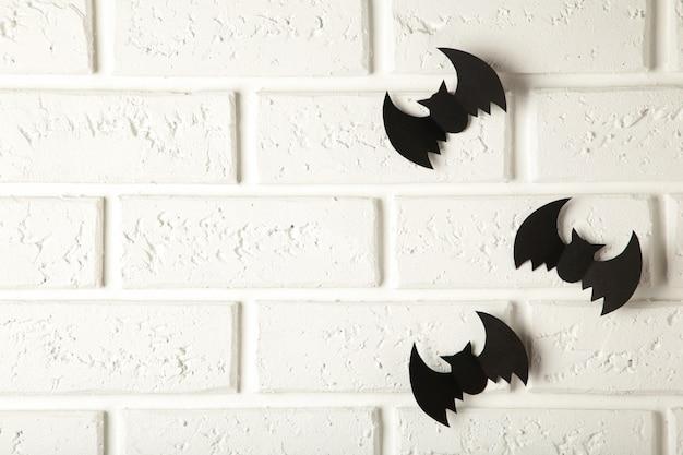 Vliegende zwarte vleermuizen over witte muur
