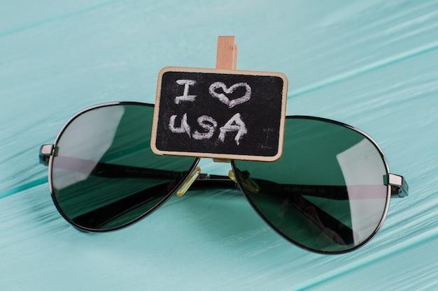 Vliegenierszonnebril met bord op blauw houten bureau. ik hou van de vs geschreven op schoolbord.