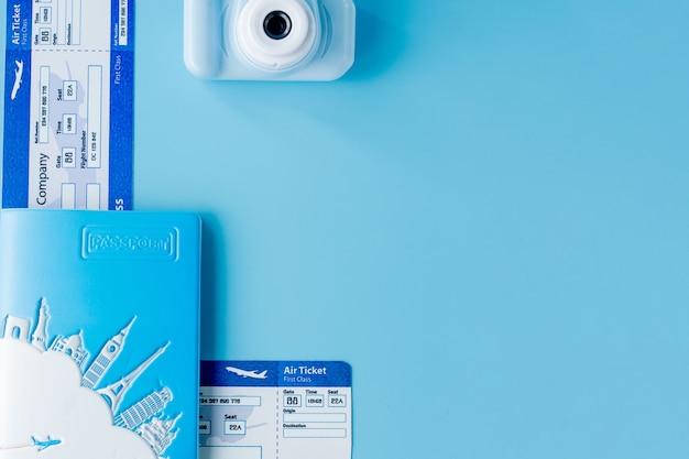 Vliegtickets met paspoorten, camera en model van vliegtuig op blauwe achtergrond. zomer of vakantie concept. ruimte kopiëren.