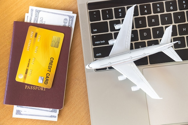 Vliegtickets, paspoorten en creditcard in de buurt van laptopcomputer en vliegtuig op tafel.
