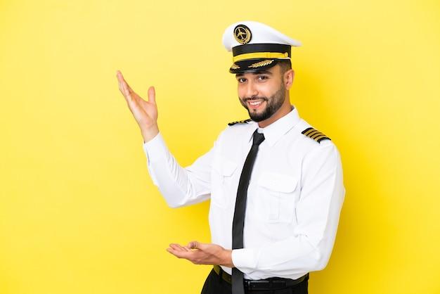 Vliegtuig arabische piloot man geïsoleerd op een gele achtergrond die zijn handen naar de zijkant uitstrekt om uit te nodigen om te komen