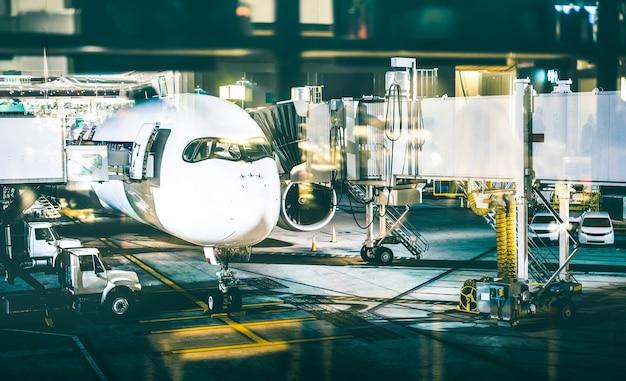 Vliegtuig bij terminalpoort die 's nachts opstijgen voorbereiden