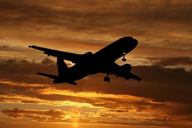 Vliegtuig dat in de zonsondergang vliegt