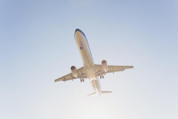 Vliegtuig dat onder blauwe hemel en witte wolk in phuket, thailand vliegt.
