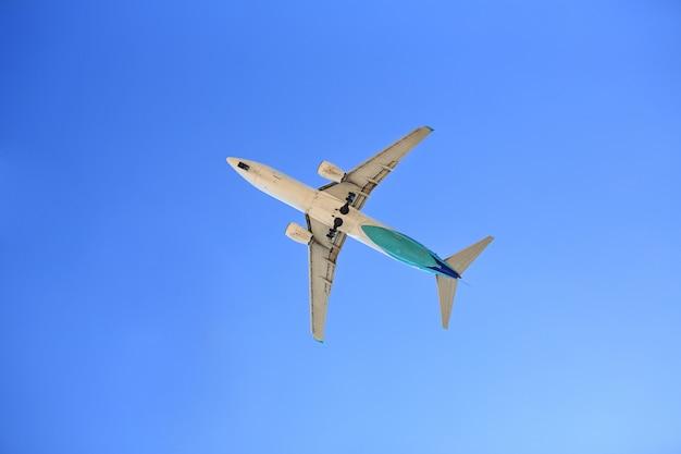 Vliegtuig dat op blauwe hemel vliegt. van onderaf gezien.