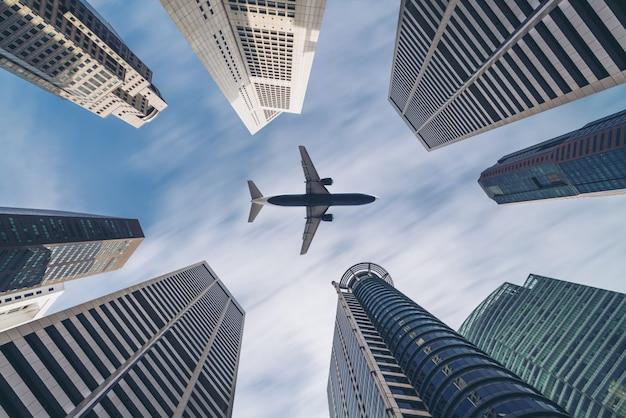 Vliegtuig dat over stads bedrijfsgebouwen vliegt, hoogbouwwolkenkrabbers