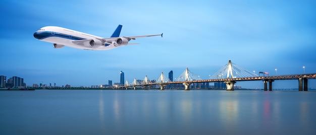 Vliegtuig dat over tropische overzees bij mooie zonsondergang of zonsopganglandschapsachtergrond vliegt