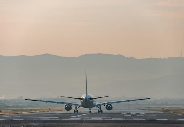 Vliegtuig dat zich 's avonds op de landingsbaan van de luchthaven bevindt.