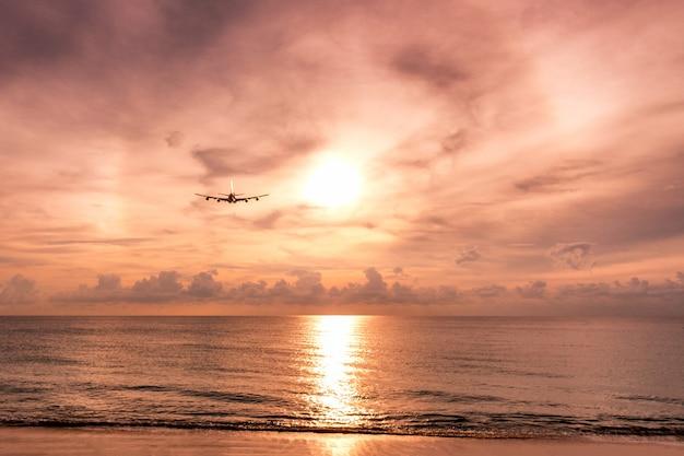 Vliegtuig die aan boogzonlicht vliegen op het overzees bij avond