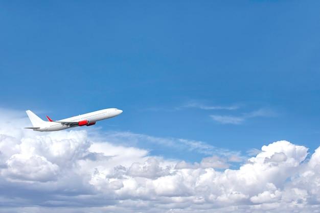 Vliegtuig die boven wolken in een blauwe hemel vliegen.