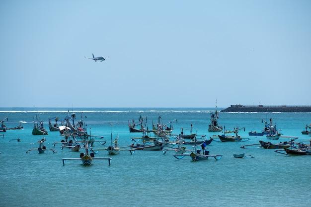 Vliegtuig die op luchthaven landen en jukung traditionele boot in bali vissen