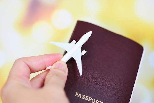 Vliegtuig en paspoort in de hand