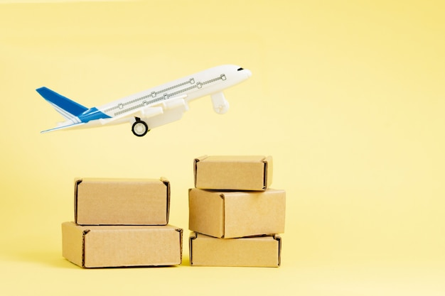Vliegtuig en stapel kartonnen dozen. concept van luchtvracht en pakketten, luchtpost. snelle levering van goederen en producten. vrachtvliegtuigen