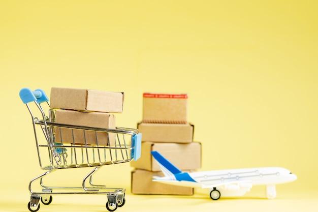 Vliegtuig en stapel kartonnen dozen. concept van luchtvracht en pakketten, luchtpost. snelle levering van goederen en producten. vrachtvliegtuigen.