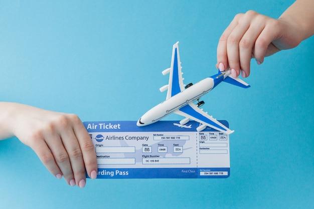 Vliegtuig en vliegticket in vrouwenhand op een blauwe achtergrond. reisconcept, exemplaarruimte.