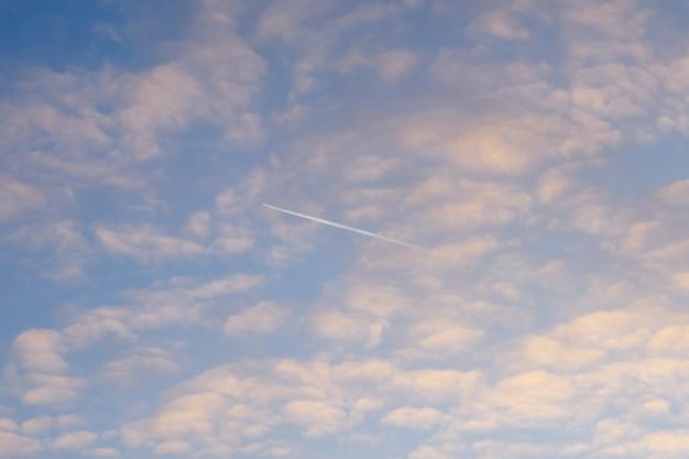 Vliegtuig in blauwe bewolkte hemel op zonsondergang.