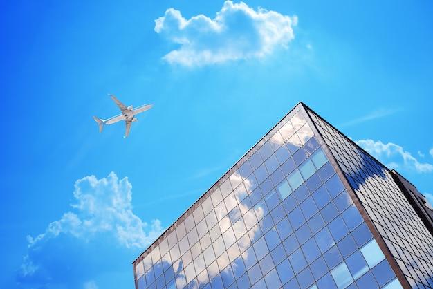 Vliegtuig in blauwe hemel met wolken dichtbij modern kantoor of luchthavengebouw