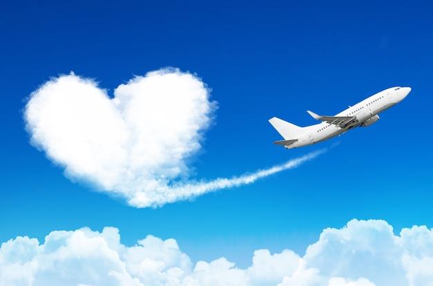 Vliegtuig in de blauwe lucht met wolken, heeft een spoor achtergelaten in de vorm van een wolk van het hart.