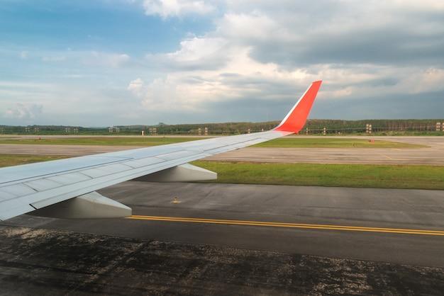 Vliegtuig in de landing van de de vleugelvleugel van de baanweg blauwe hemel in luchthaven.