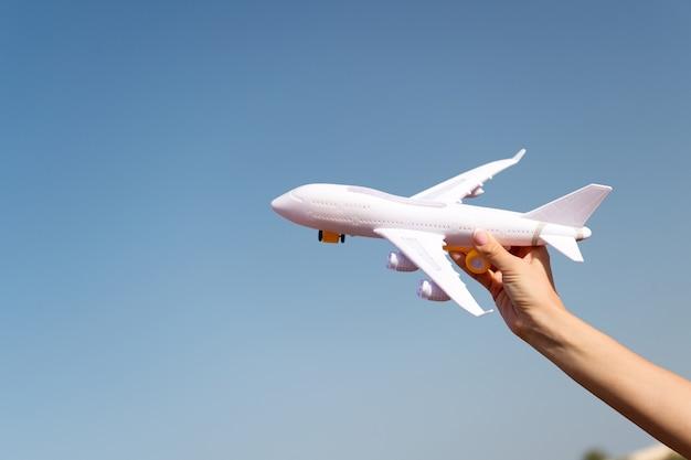 Vliegtuig in vrouwelijke hand heldere blauwe hemel achtergrond kopie ruimte. reizen en vakantie. boek nu tickets. speelgoed witte vliegtuig vlieg vakantiebestemmingen. reis comfortabele premiumklasse luchtvaartmaatschappijen. ontdek wereld.