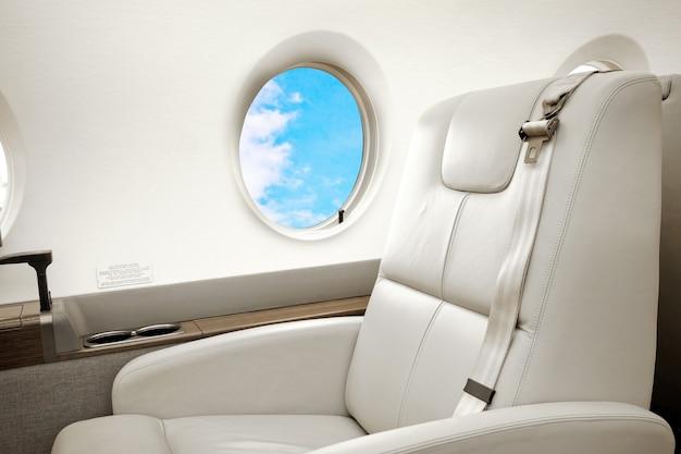 Vliegtuig (jet) business class interieur met blauwe lucht buiten de patrijspoort